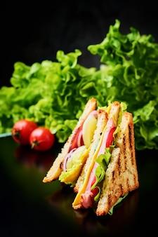 Panini con prosciutto, lattuga e verdure fresche su uno sfondo scuro