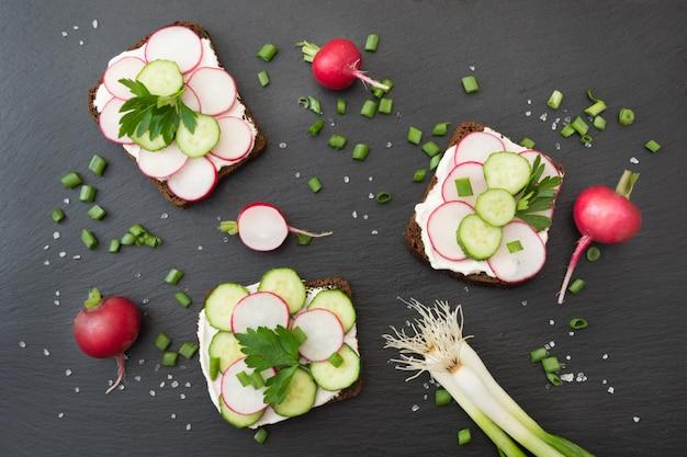Panini con ravanello, cetriolo, cipolla su un pane di segale.