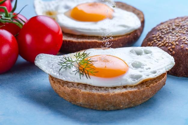 Panini con uova di gallina fatte in casa e fritte cosparse di spezie e sale per una colazione su una superficie blu. alimento proteico. panini con uova