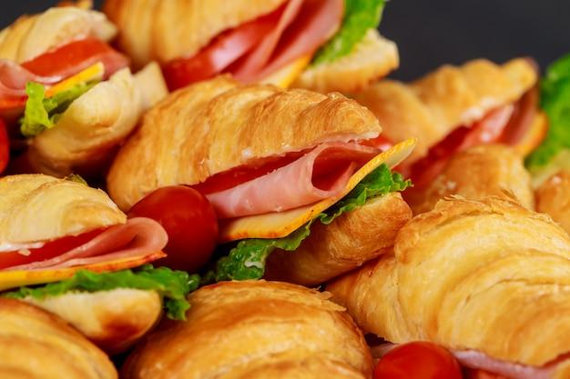 Panini del croissant con il prosciutto e la lattuga, primo piano