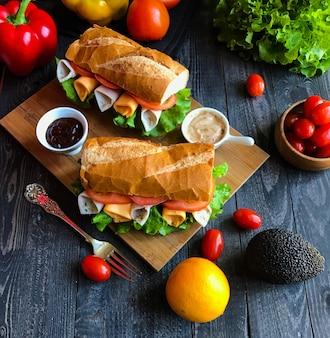Panini deliziosi e gustosi con tacchino, prosciutto, formaggio, pomodori