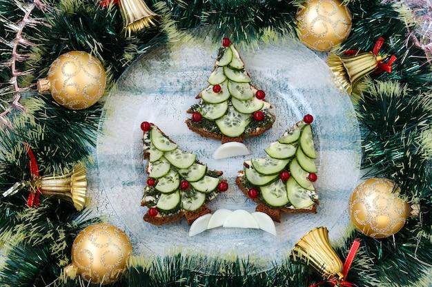 Panini di capodanno con pane nero, formaggio e cetrioli a forma di albero di natale, bacche decorate