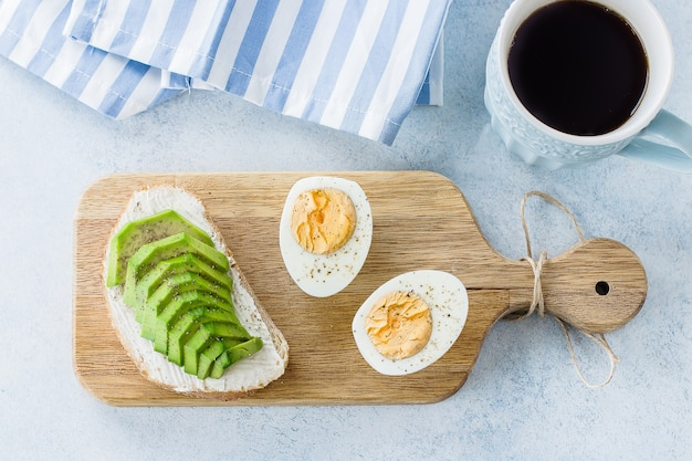 Panini di pane integrale con avocado e uova sode su tavola di legno e caffè