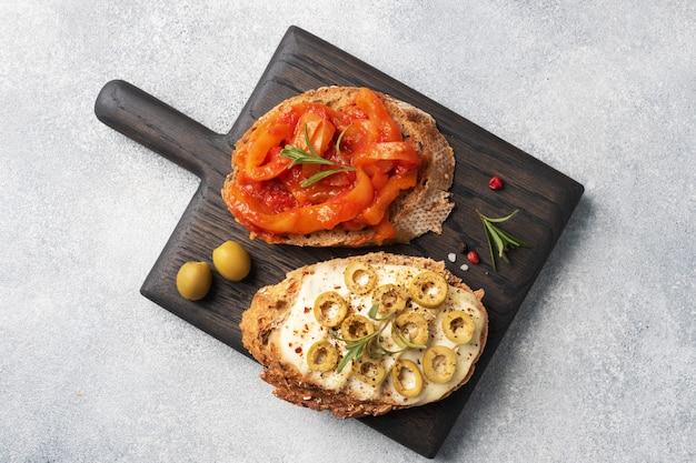 Panini di pane integrale con crema di formaggio, olive e peperoni in scatola con pomodoro su un tagliere di legno.