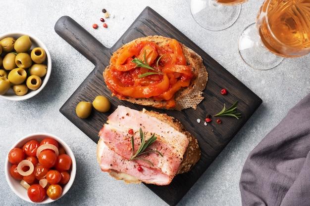 Panini di pane integrale con crema di formaggio, pancetta e peperoni in scatola con pomodoro su un tagliere di legno.