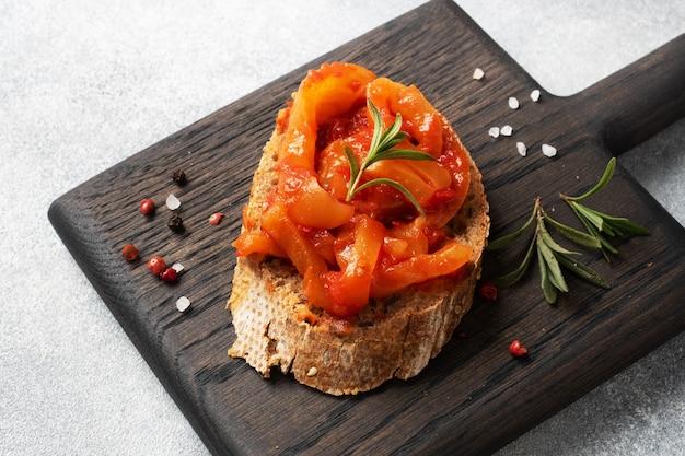 Panini di pane integrale con peperoni in scatola con pomodoro su un tagliere di legno.