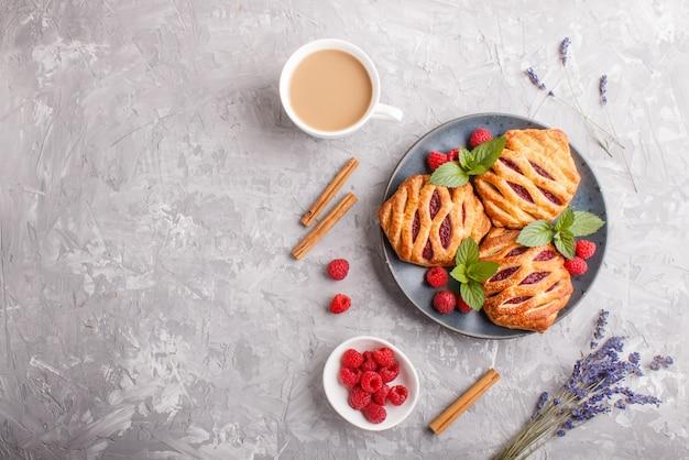 Panini di pasta sfoglia con marmellata di fragole sul piatto in ceramica blu su sfondo grigio cemento