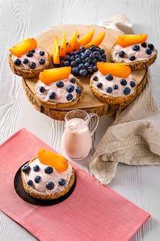 Panini dolci con formaggio a pasta molle, mirtillo e fetta di cachi sulla tavola di legno bianca