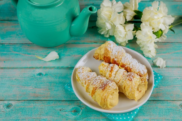 Panini dolci croccanti con panna montata, teiera e fiori.