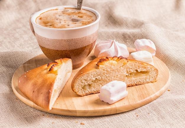 Panini dolci, meringhe e tazza di caffè su una tavola di legno