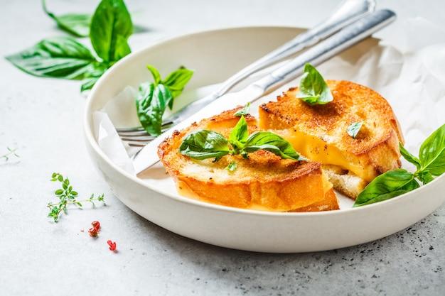 Panini fritti con formaggio e basilico sul piatto bianco.