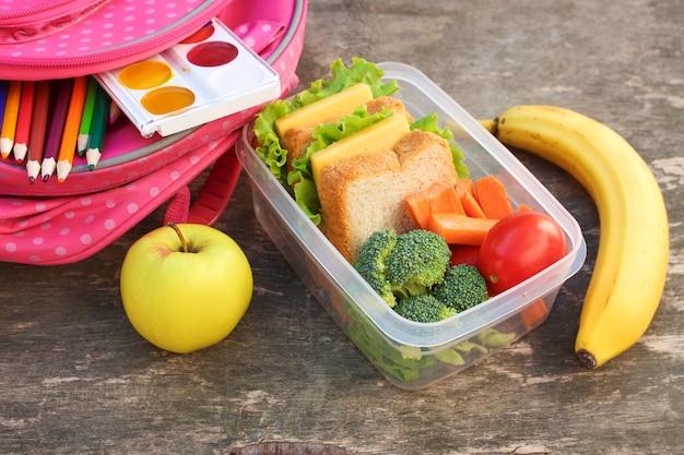 Panini, frutta e verdure in scatola di cibo, zaino su fondo in legno vecchio.