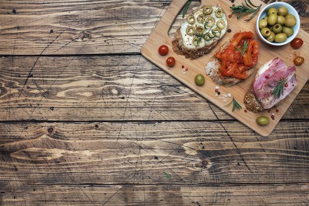 Panini integrali con crema di formaggio, pancetta e olive in scatola peperoni con pomodoro su fondo in legno. copia spazio.