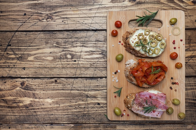 Panini integrali con crema di formaggio, pancetta e olive in scatola peperoni con pomodoro su fondo in legno.