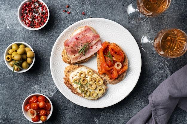 Panini integrali con crema di formaggio, pancetta e olive in scatola peperoni con pomodoro su un piatto.
