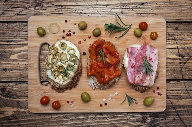 Panini integrali con crema di formaggio, pancetta e olive peperoni in scatola con pomodoro