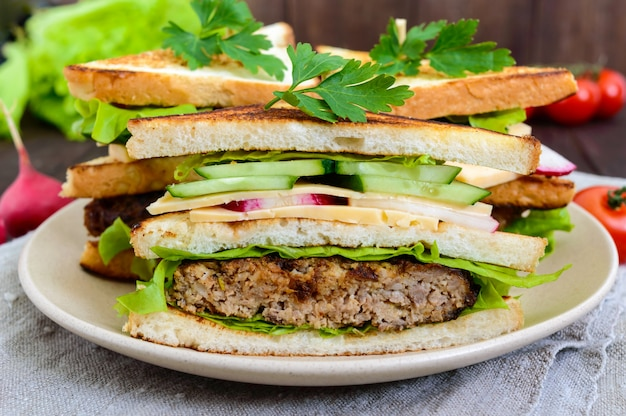 Panini multistrato con una succosa cotoletta, formaggio, ravanello, cetriolo, lattuga, rucola che tagliano a metà su un piatto su un fondo di legno scuro. avvicinamento