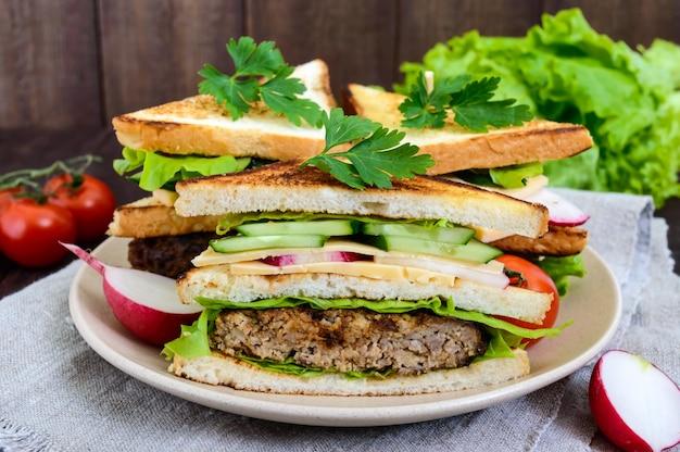 Panini multistrato con una succosa cotoletta, formaggio, ravanello, cetriolo, lattuga, rucola che tagliano a metà su un piatto su un fondo di legno scuro.