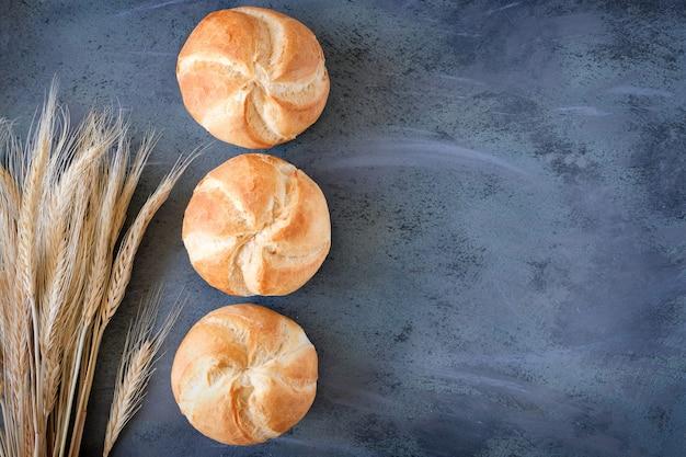 Panini rotondi croccanti, conosciuti come kaiser o rotoli di vienna con un mazzo di spighe di grano su sfondo grigio