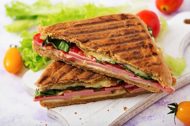 Panini sandwich club con prosciutto, pomodoro, formaggio e lattuga
