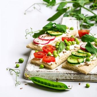 Panini sani con formaggio a pasta molle e verdure crude su pane croccante.