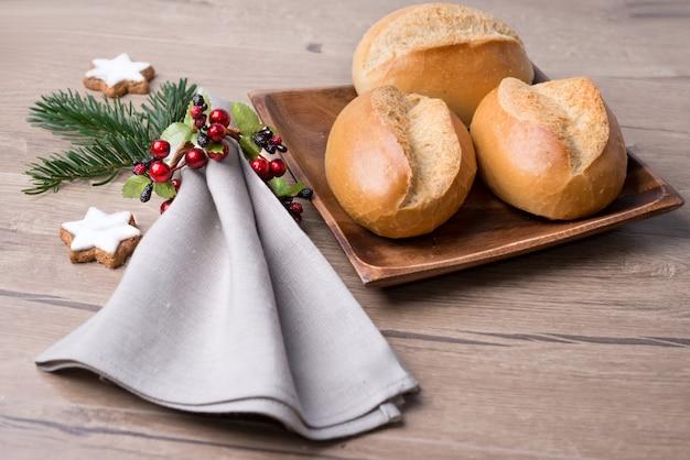Panini sul piatto di legno con il tovagliolo e le decorazioni di natale