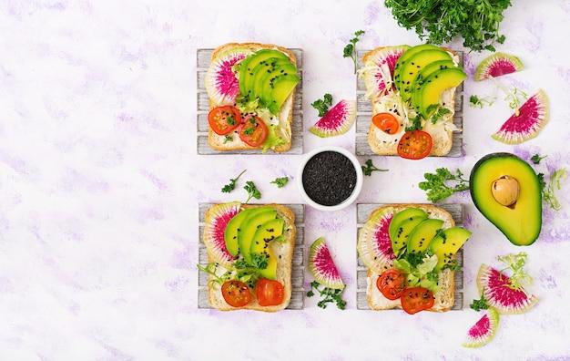 Panini vegani con avocado, ravanello anguria e pomodori su uno sfondo bianco