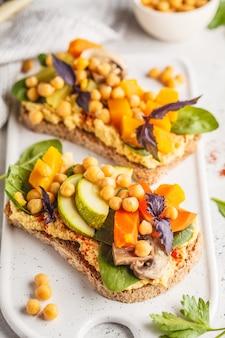 Panini vegani sani con hummus, ceci, verdure al forno e basilico sul bordo bianco.