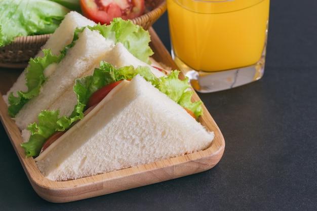 Panino al formaggio prosciutto con lattuga e pomodoro sul piatto di legno servito con succo d'arancia