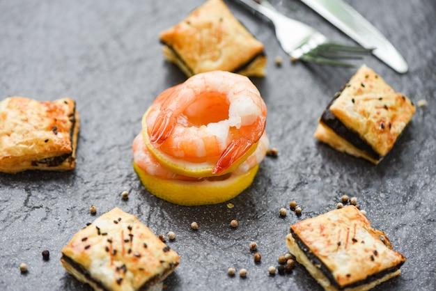 Panino al limone con gamberi freschi servito sul piatto scuro, gamberi bolliti pelati scampi cucinati con spezie e bignè al sesamo nel ristorante di pesce