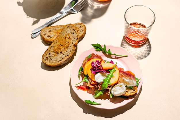 Panino al prosciutto di parma, mozzarella e pesche su un piatto, un po 'di pane e vino rosato girato con luce intensa