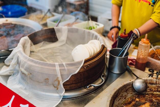 Panino al vapore bianco in cesto di bambù con pancia di maiale brasato caldo