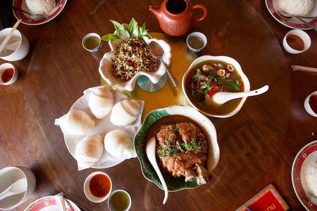 Panino al vapore e coscia di maiale in umido nel sugo e zuppa di pollo nero con erbe cinesi, cibi yunnan sul tavolo.