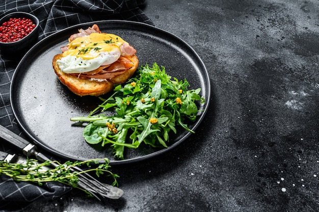 Panino alla brioche con pancetta, uovo alla benedict e salsa olandese. guarnire con insalata di rucola. sfondo nero. vista dall'alto. copia spazio
