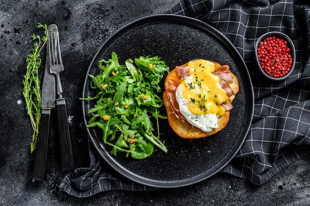 Panino alla brioche con pancetta, uovo alla benedict e salsa olandese. guarnire con insalata di rucola. sfondo nero. vista dall'alto