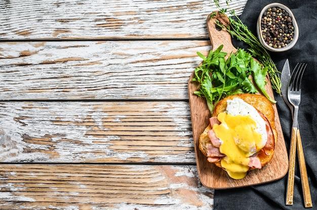 Panino alla brioche con pancetta, uovo alla benedict e salsa olandese. sfondo bianco. vista dall'alto. copia spazio