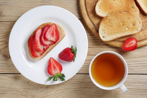 Panino alla fragola e tazza di tè sulla tavola di legno, vista superiore