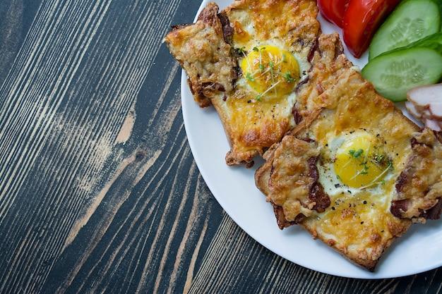 Panino alla griglia con uovo, verdure e pancetta su un fondo di legno scuro