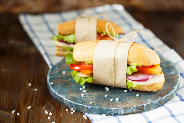 Panino appetitoso da pane croccante con pollo, pomodori, lattuga, formaggio e spezie su un fondo di legno scuro.