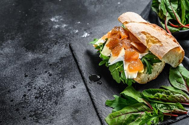 Panino baguette con formaggio di capra, marmellata di pere, bietole e spinaci. sfondo nero. vista dall'alto. copia spazio