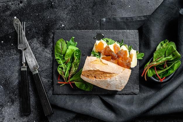 Panino baguette con formaggio di capra, marmellata di pere, bietole e spinaci. sfondo nero. vista dall'alto