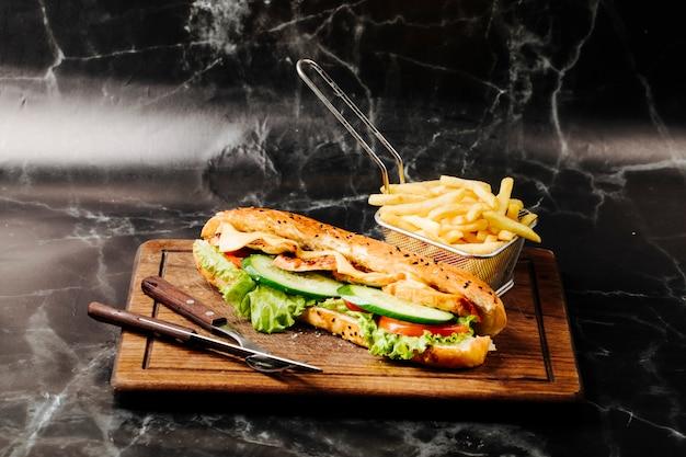 Panino baguette con ingredienti misti e patatine fritte su una tavola di legno.