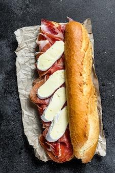 Panino baguette con prosciutto jamon serrano, paleta iberica, formaggio camembert. sfondo nero, vista dall'alto.