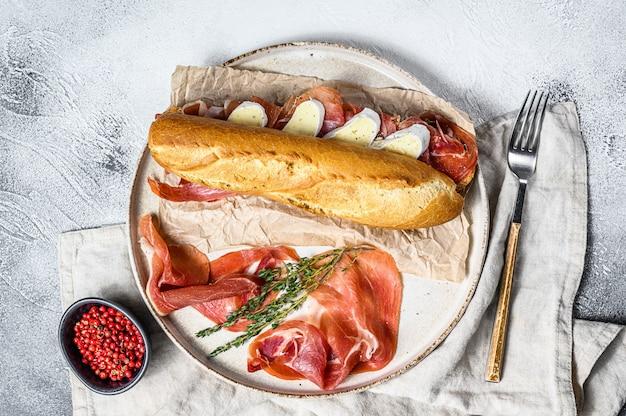 Panino baguette con prosciutto jamon serrano, paleta iberica, formaggio camembert sul tagliere. , vista dall'alto.