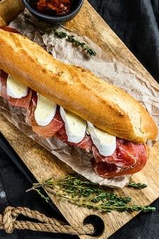 Panino baguette con prosciutto jamon serrano, paleta iberica, formaggio camembert sul tagliere.