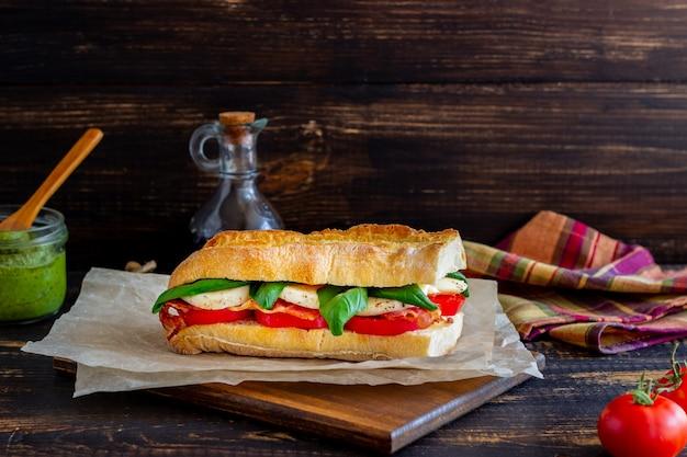 Panino caprese con pomodoro, mozzarella, basilico e pancetta. mangiare sano. cucina italiana.