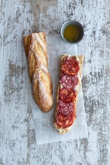 Panino ciabatta con pesto, erbe aromatiche, prosciutto, salame, salsiccia, mozzarella e spinaci su legno grigio, vista dall'alto