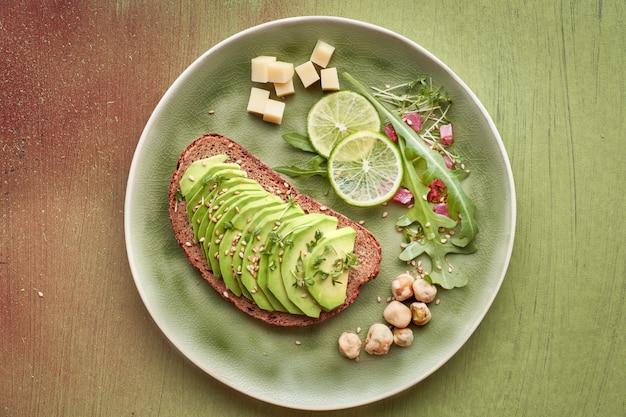 Panino con avocado e insalata verde con cubetti di prosciutto