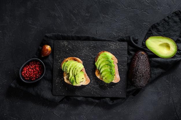 Panino con avocado maturo. sfondo nero. vista dall'alto