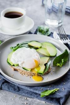 Panino con avocado, spinaci e uovo in camicia su pane integrale sul piatto sul retro di pietra